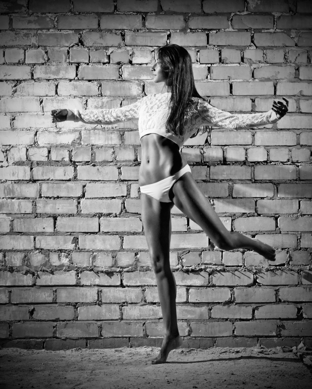 Young dancing woman on brick wall background (monochrome ver)